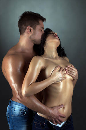 Tanned passionate lovers embracing in studio, close-up photo