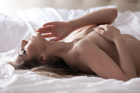 naked women: Portrait of excited young woman lying on hotel bed, close-up