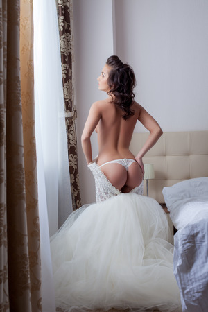 Beautiful slim girl takes off her wedding dress in hotel room photo