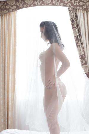 Image of slender bride posing naked in hotel room photo