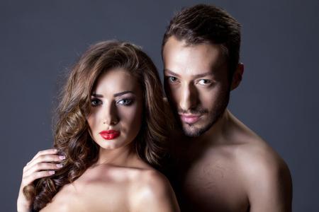 naked young women: Портрет красивых молодых людей позируют обнаженными в студии Фото со стока