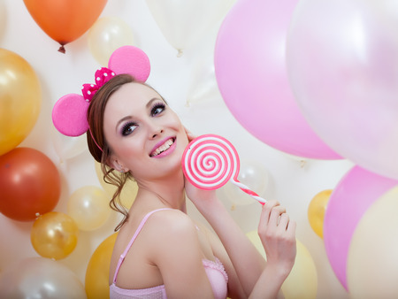 comely: Portrait of smiling comely girl posing with lollipop