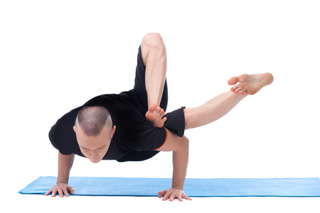 asana: Studio shot of flexible middle-aged man posing in asana