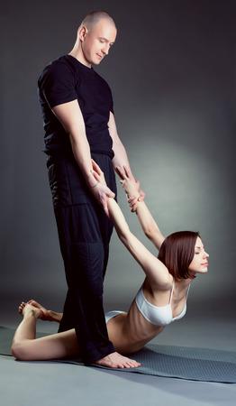helps: Studio shot of experienced instructor helps girl in yoga