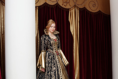 actress: Young actress in royal dress posing on curtain backdrop Stock Photo