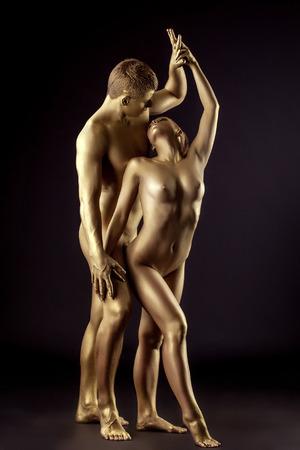 mujeres eroticas: Pareja de amantes jóvenes como estatua de oro, posando en estudio