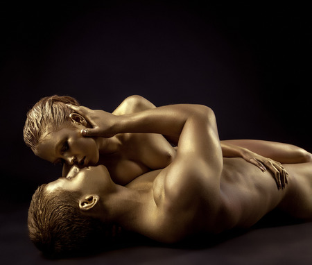 naked statue: Couple of naked lovers posing as golden statues come to life Stock Photo