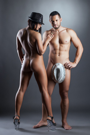Hot young dancers posing naked in hats, on gray background Stock Photo