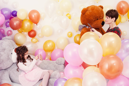 balloon animals: Elegant mother photographed her charming daughter in studio with balloons