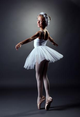 Elegant little girl dancing role of White Swan photo