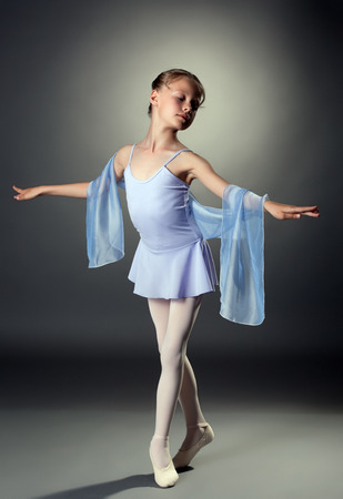 Charming little dancer posing in studio, on gray background