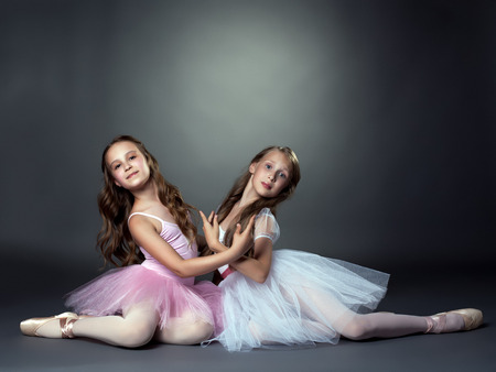 Studio shot of two graceful ballet dancers, on gray background