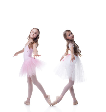 pointe: Two pretty girlfriends-ballerinas posing at camera, isolated on white