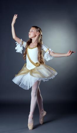 Studio shot of elegant young ballerina posing at camera photo