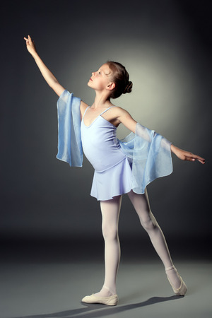 ballet clásico: Imagen de la pequeña bailarina agraciada que presenta en gris telón de fondo Foto de archivo