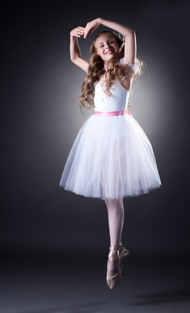 Image of emotional young ballet dancer posing in jump