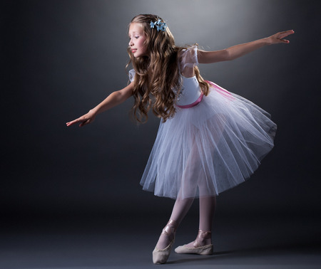 Image of charming curly girl dancing ballet in studio photo