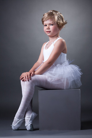 Studio shot of adorable girl posing in tutu, on gray background