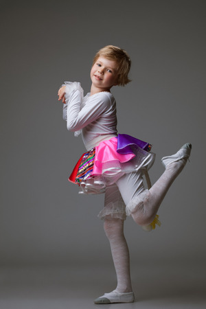 Image of playful little ballerina posing at camera