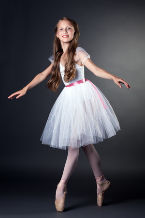 Beautiful teen long-haired ballerina dancing in studio
