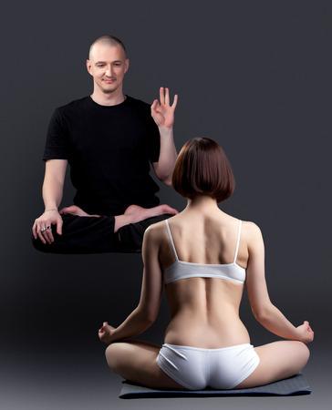 meditates: Image of smiling levitating man looks at woman meditates