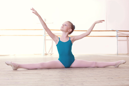Image of flexible little ballerina posing sitting on split photo