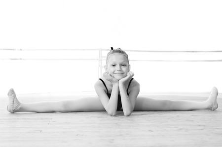 Black and white photo  Smiling ballerina doing gymnastic split Archivio Fotografico