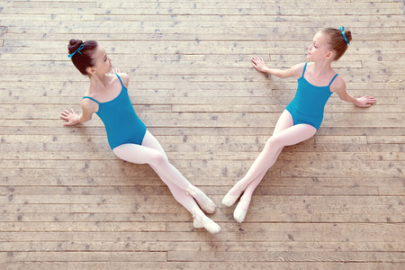 Two little ballerinas posing on wooden floor in dance studio photo