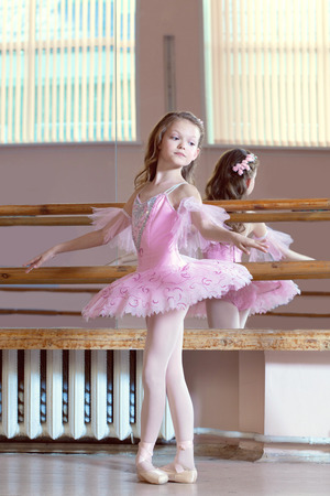 Studio shot of petite ballerina posing in pink tutu