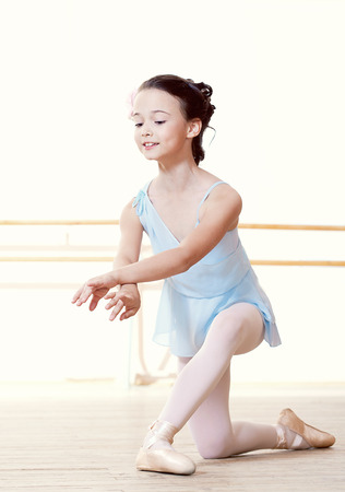 Pretty little dancer doing exercises in ballet studio