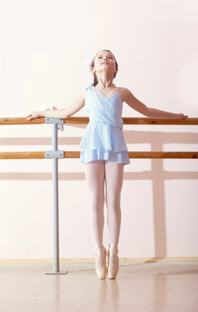 Image of petite ballerina doing exercises in dance class photo