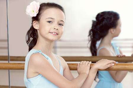 Portrait of pretty dark-haired ballerina posing with barre Stock Photo