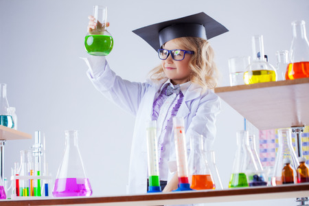 reagents: Young chemist posing with variety of reagents in lab, close-up