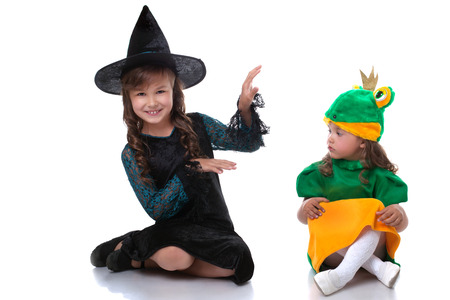 charming girl: Cute little sisters posing in costumes of witch and frog Stock Photo