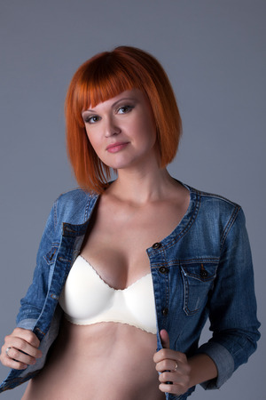 Hot redhead girl posing in seamless bra and denim jacket photo