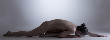 naked statue: Image of nude woman with glowing skin posing lying in studio Stock Photo