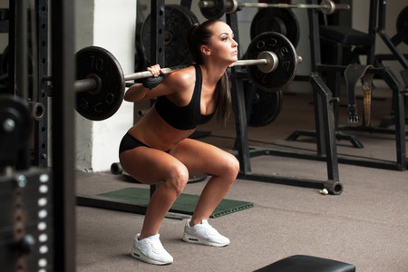 barbell: Beautiful young girl exercising squatting with barbell