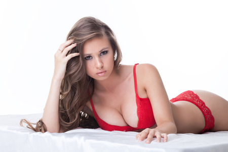 Portrait of busty brunette posing in red lingerie