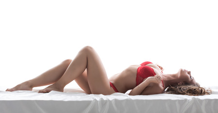 Image of excited slim model posing lying in red lingerie Stock Photo