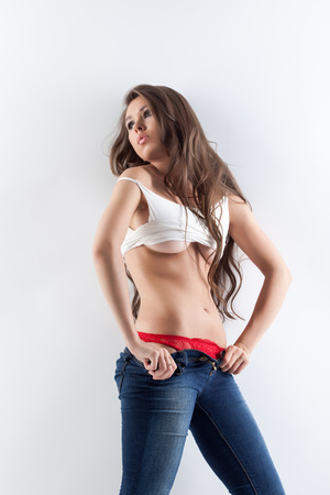 Seductive young model posing in t-shirt and unbuttoned jeans photo