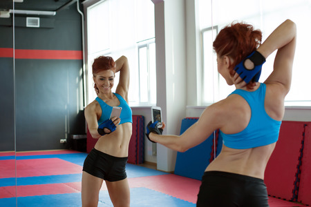 Amusing sporty girl photographing herself in mirror photo