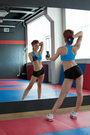 Skinny girl photographing herself in fitness center photo