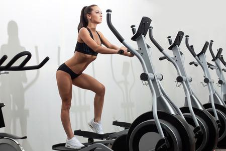 Image of beautiful young woman exercising on ski simulator
