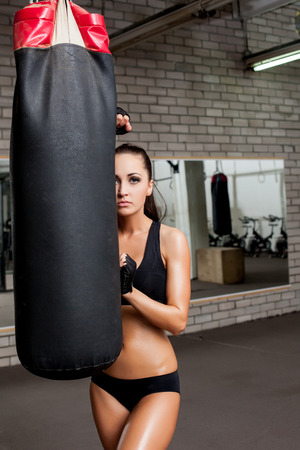 punched: Tanned female athlete looks out from behind punching bag