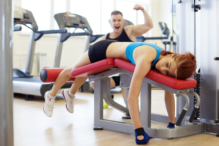 tired man: Image of merry man and woman tired of training in gym