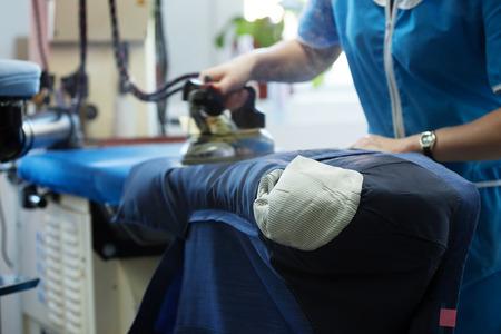 Werken in wasruimte - beeld van de vrouw strijken nieuw jasje