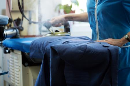 Afbeelding van wasserij werknemer stomen jas op de strijkplank
