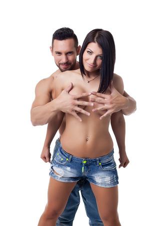 senos desnudos: Hombre alegre cubre con las manos los pechos desnudos de su novia