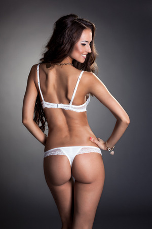 women in underwear: Rear view of smiling tanned model in white lingerie