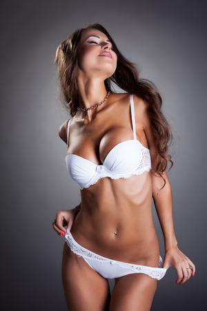 Seductive tanned model posing in white lingerie, on gray backdrop